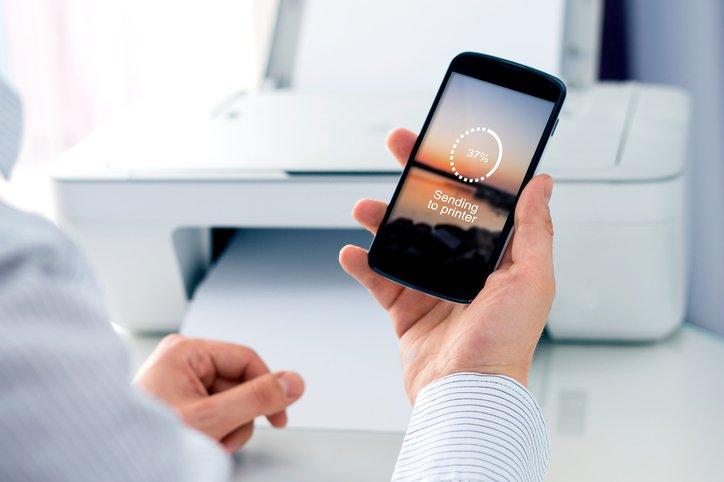 Man sending a photo to wireless printer